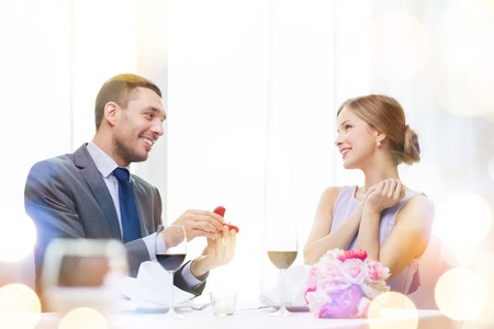 restaurant, couple and holiday concept - smiling man proposing to his girlfriend at restaurant photo