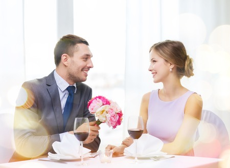 restaurant, couple and holiday concept - smiling man giving girlfriend or wife bouquet of flowers at restaurant photo