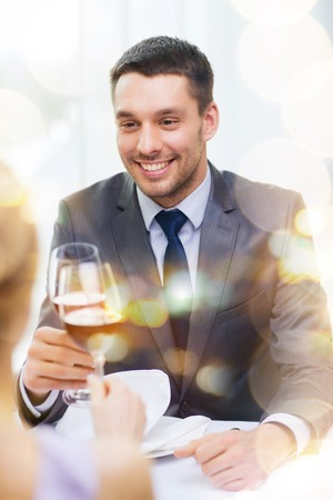 restaurant, couple and holiday concept - smiling young man with glass of red wine looking at girlfriend or wife at restaurant photo