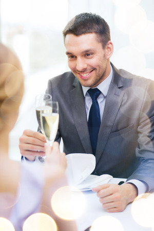 clinking: restaurant, couple and holiday concept - smiling man with glass of champagne looking at wife or girlfriend at restaurant