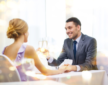 restaurant, couple and holiday concept - smiling man with glass of champagne looking at wife or girlfriend at restaurant photo
