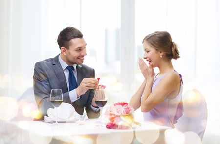 wedding anniversary: restaurant, couple and holiday concept - smiling man proposing to his girlfriend at restaurant Stock Photo