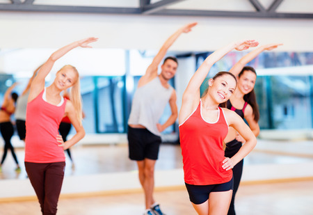 fitness, sport, training, gym and lifestyle concept - group of smiling people stretching in the gym photo