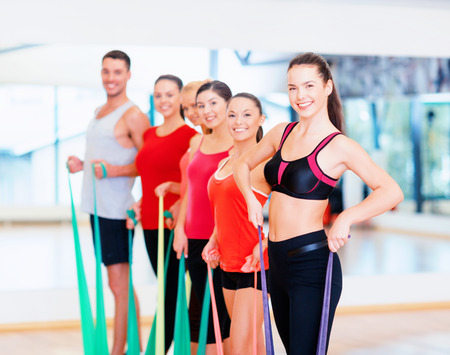 elastic: fitness, sport, training, gym and lifestyle concept - group of smiling people working out with rubber bands in the gym Stock Photo