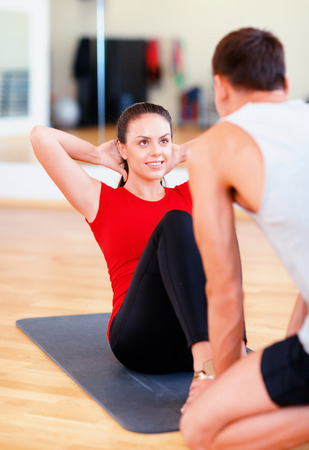 sit ups: fitness, sport, training, gym and lifestyle concept - male trainer with woman doing sit ups
