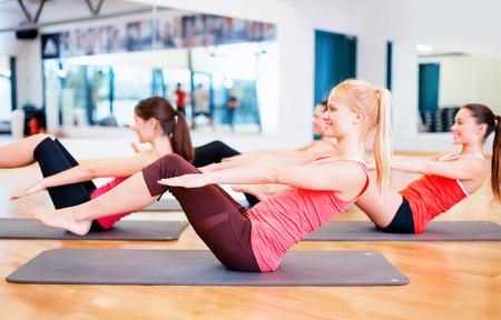 피트 니스, 스포츠, 교육, 체육관 및 라이프 스타일 개념 - 체육관에서 매트에 운동하는 웃는 여자의 그룹