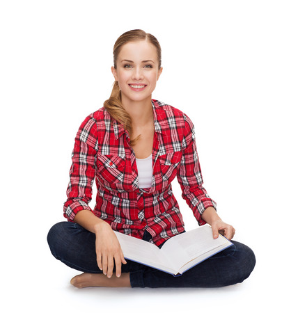 education and leisure concept - smiling young woman sitting on floor with book photo