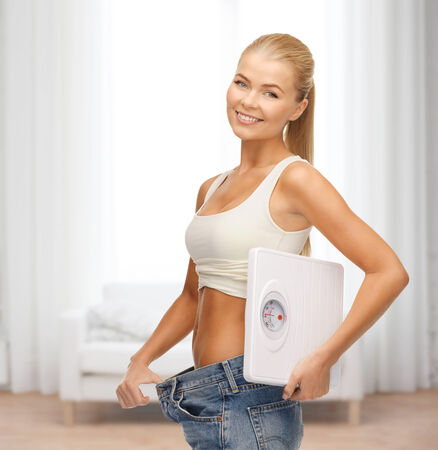 fitness, diet and healthcare concept - sporty woman showing big pants and holding scales
