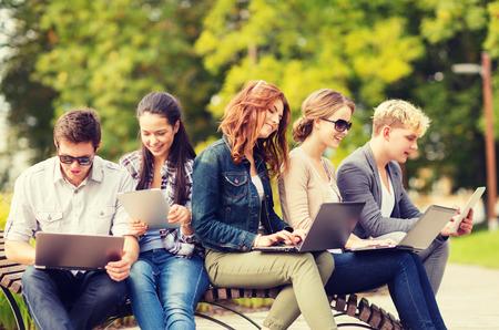 zomer, internet, onderwijs, campus en teenage concept - groep studenten of tieners met laptop en tablet computers opknoping uit Stockfoto