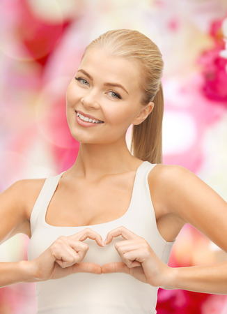 love, happiness and people concept - smiling woman showing heart shape gesture photo