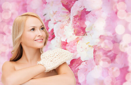 exfoliation: health, spa and beauty concept - smiling woman with exfoliation glove Stock Photo