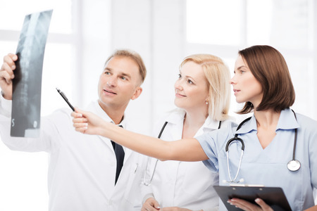 radiology: healthcare, medical and radiology concept - doctors looking at x-ray