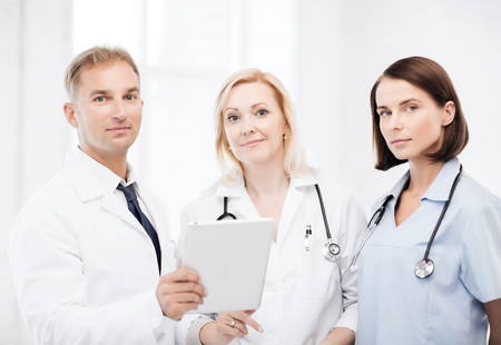healthcare and technology concept - doctors looking at tablet pc photo
