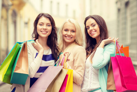 shopping, sale, happy people and tourism concept - beautiful girls with shopping bags in ctiy photo