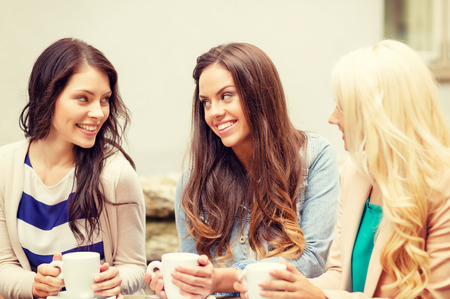 holidays, food and tourism concept - three beautiful girls drinking coffee in cafe photo
