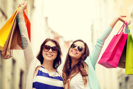 shopaholics: shopping, sale, happy people and tourism concept - smiling girls in sunglasses with shopping bags in ctiy