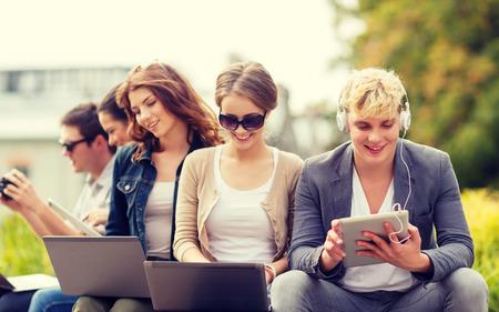 junge nackte frau: Sommer, Internet, Bildung, Campus und Teenager-Konzept - Gruppe von Studenten oder Jugendliche mit Laptop und Tablet-Computer hängen