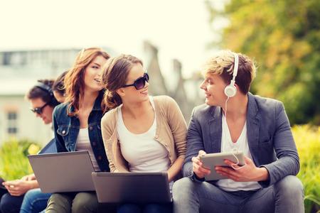 zomer, internet, onderwijs, campus en tiener concept - groep studenten of tieners met laptop en tablet computers opknoping uit Stockfoto