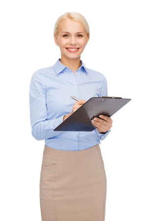 taking notes: business and education concept - friendly young smiling businesswoman with clipboard and pen