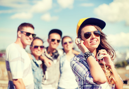 summer holidays and teenage concept - teenage girl in sunglasses, cap and headphones hanging out with friends outside photo