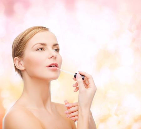lipgloss: cosmetics, health and beauty concept - beautiful woman with pink lipgloss