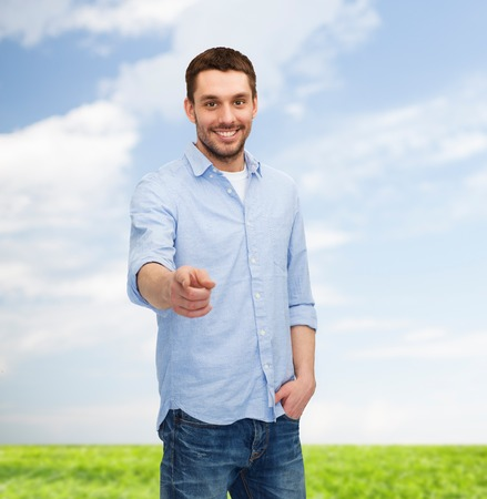 happiness and people concept - smiling man pointing finger at you photo