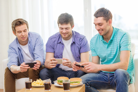 friendship, technology, food and leisure concept - smiling friends taking picture of food with smartphone camera at home photo