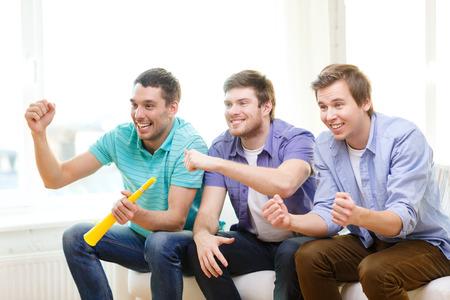 ver tv: amistad, deportes y entretenimiento - amigos hombres felices con vuvuzela ver deportes en casa Foto de archivo
