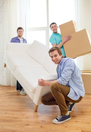 moving, real estate and friendship concept - smiling male friends with sofa and boxes at new home photo