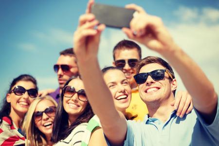 여름, 휴일, 휴가 및 행복 개념 - 스마트 폰으로 사진을 촬영하는 친구의 그룹 스톡 콘텐츠