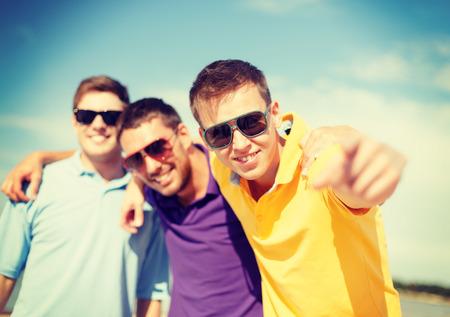 gar�on souriant: �t�, vacances, vacances et le concept de bonheur - groupe d'amis amusent sur la plage et pointant � vous