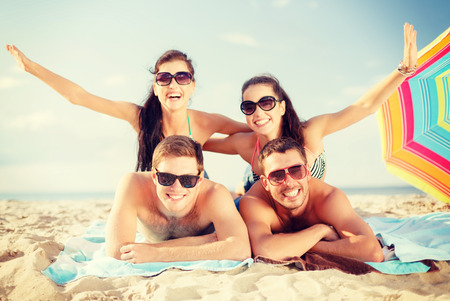 chilling out: summer, holidays, vacation and happy people concept - group of smiling people in sunglasses having fun on the beach Stock Photo