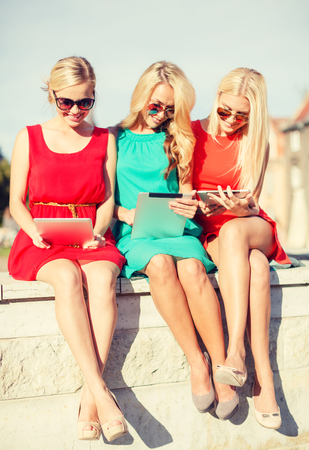holidays and tourism concept - beautiful blonde girls toursits looking into tablet pcs in the city photo