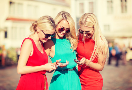 bachelorette party: holidays and tourism, modern technology concept - beautiful blonde girls with smartphones in the city Stock Photo
