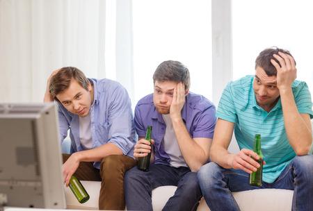 友情、スポーツ、エンターテイメントのコンセプト - ビールを自宅のテレビでスポーツを見ていると悲しいの男性の友人