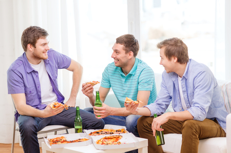 nonalcoholic beer: friendship, food and leisure concept - smiling male friends with beer and pizza hanging out at home