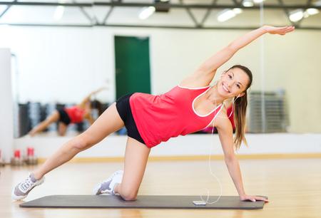 fitness, deporte, entrenamiento, gimnasio, tecnología y estilo de vida concepto - sonriente adolescente con celular y los auriculares en el gimnasio