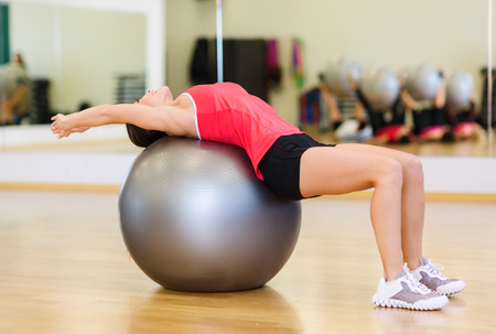 fit ball: fitness, sport, training, gym and lifestyle concept - young woman doing exercise on fitness ball