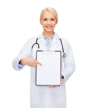 healthcare and medicine concept - smiling female doctor with stethoscope pointing finger to clipboard and blank page photo