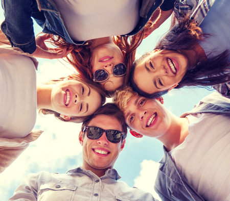 hanging woman: summer holidays and teenage concept - group of teenagers looking down Stock Photo