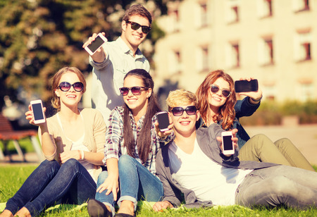 education, technology, internet, summer holidays, social networking and teenage concept - group of teenagers with smartphones photo