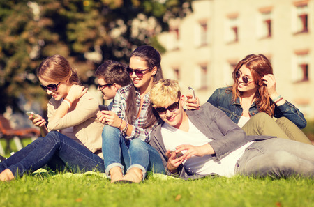 college campus: education, technology, internet, summer holidays, social networking and teenage concept - group of teenagers with smartphones