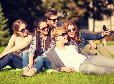 group picture: summer holidays and teenage concept - group of teenagers taking photo outside with smartphone