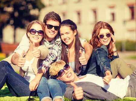 chilling out: summer holidays, education, campus and teenage concept - group of students or teenagers showing thumbs up