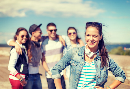 teenagers laughing: summer holidays and teenage concept - teenage girl in sunglasses and headphones hanging out with friends outside