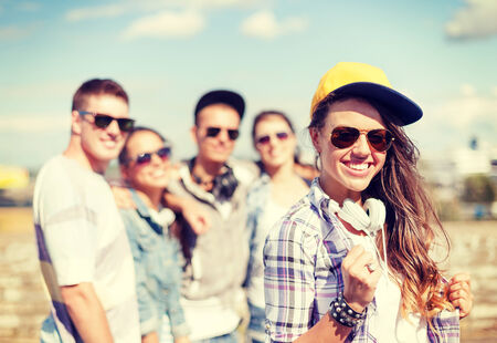 chilling out: summer holidays and teenage concept - teenage girl in sunglasses, cap and headphones hanging out with friends outside