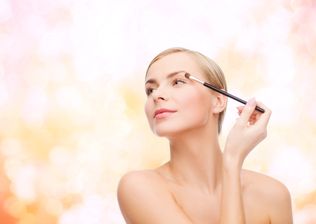 sensitive skin: cosmetics, health and beauty concept - beautiful woman with makeup brush Stock Photo