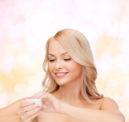health, beauty and spa concept - beautiful woman applying cream photo