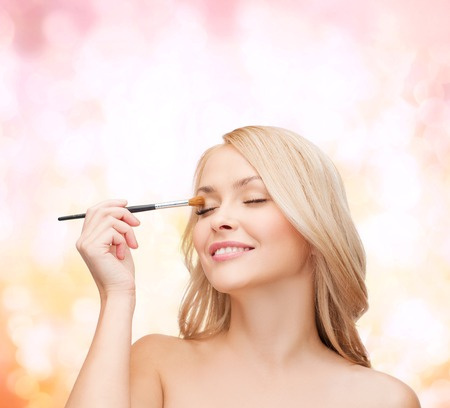 eyelid: cosmetics, health and beauty concept - beautiful woman with closed eyes and makeup brush Stock Photo