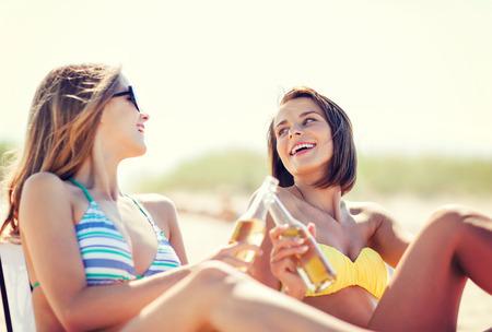 niñas en bikini: vacaciones de verano y vacaciones - chicas en bikini con bebidas en las sillas de playa Foto de archivo